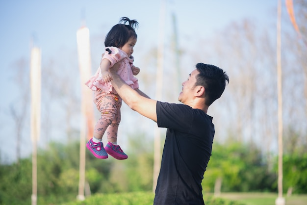 Retrato de bebê fofo e o pai dela viajam no jardim de flores Foto Premium