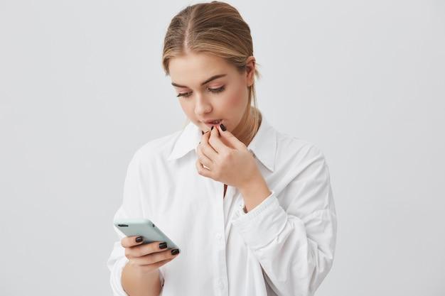 Retrato de bela aluna caucasiana vestida casualmente segurando o telefone celular, se comunicar com os amigos através de redes sociais, usando a conexão de internet alta, tocando seus lábios. Foto gratuita