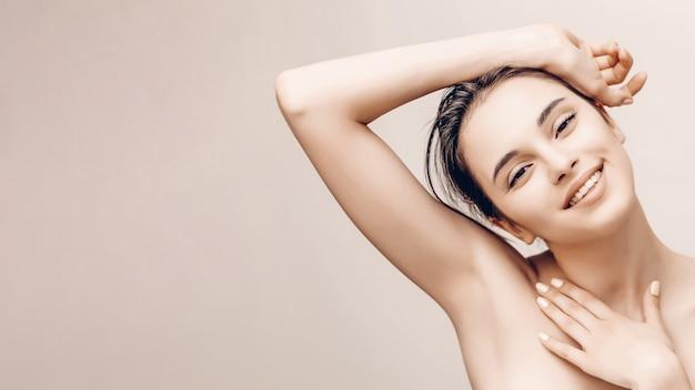 Retrato de beleza natural do rosto feminino e corpo com pele perfeita. publicidade desodorizante e conceito de depilação capilar Foto Premium
