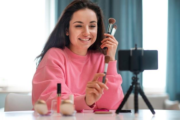 Retrato de blogueiro gravando vídeo com acessórios de maquiagem Foto Premium