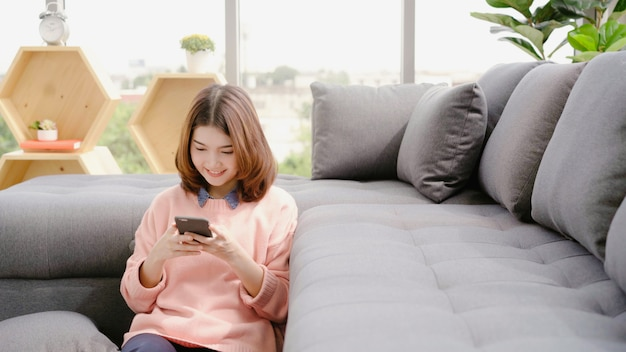 Retrato, de, bonito, atraente, jovem, sorrindo, mulher asian, usando, smartphone Foto gratuita