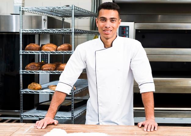 Retrato de bonito baker na padaria com pães e forno no fundo Foto gratuita