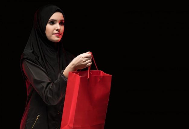 Retrato, de, bonito, esperto, jovem, muçulmano, mulher, desgastar, pretas, hijab, oferecendo, saco shopping, como, assistente loja, ligado, pretas Foto Premium