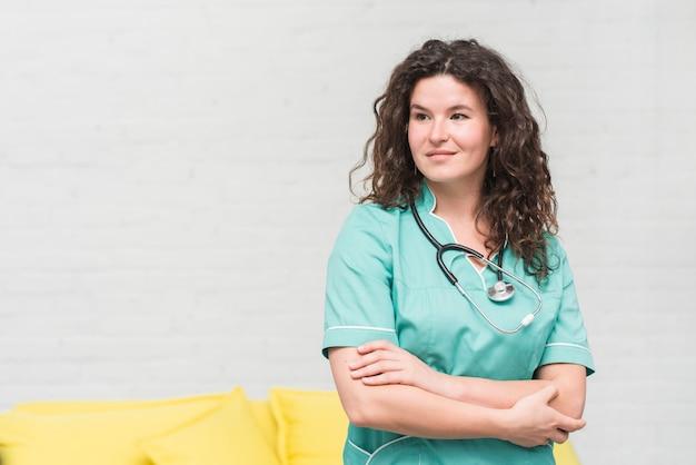 Retrato, de, bonito, femininas, enfermeira, contra, branca, parede Foto gratuita