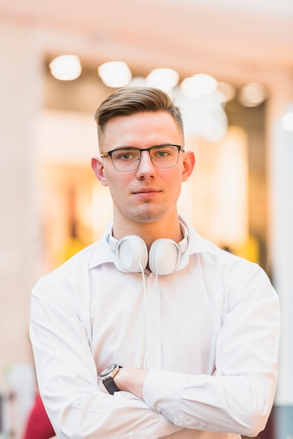 Retrato, de, bonito, homem jovem, com, braços cruzaram, segurando, branca, headphone, ao redor, seu, pescoço Foto gratuita