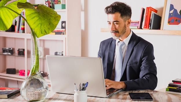 Retrato, de, bonito, homem negócios, usando computador portátil, em, seu, local trabalho Foto gratuita