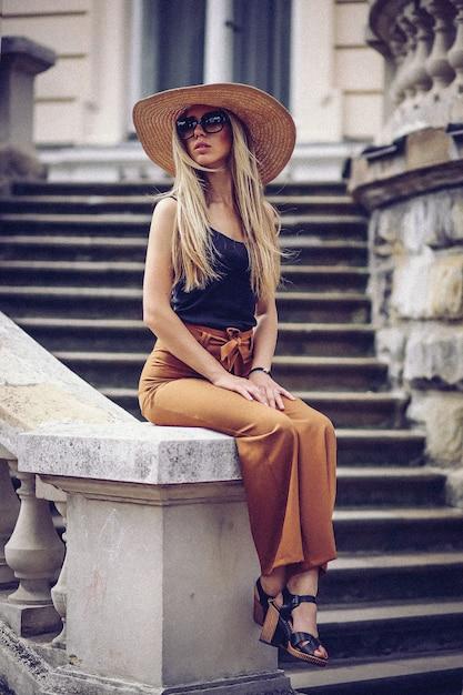 Retrato, de, bonito, legal, menina, gesticule, em, chapéu, e, óculos de sol, sobre, grunge, parede Foto Premium