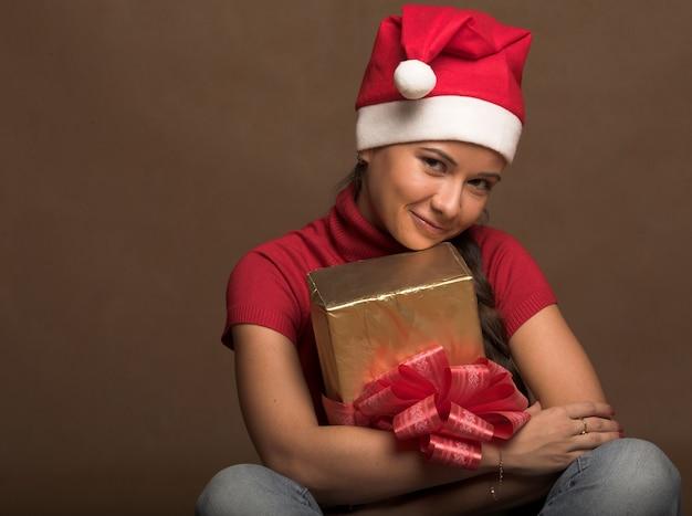 Retrato, de, bonito, mulher jovem, desgastar, papai noel, chapéu, com, presente Foto Premium