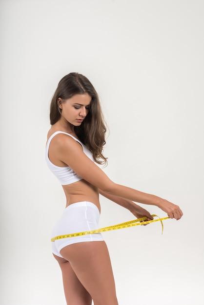 Retrato, de, bonito, mulher jovem, medindo, dela, figura, tamanho, com, fita métrica Foto gratuita