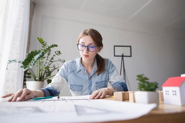 Retrato, de, bonito, mulher jovem, trabalhando, ligado, blueprint, em, lugar funcionamento Foto gratuita