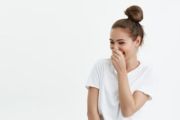 Retrato de brincalhão mulher caucasiana feminina rindo enquanto olha para o espaço da cópia e cobrindo a boca com a mão Foto gratuita
