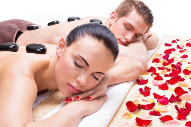 Retrato de casal atraente relaxante no salão spa com pedras quentes no corpo. Foto gratuita