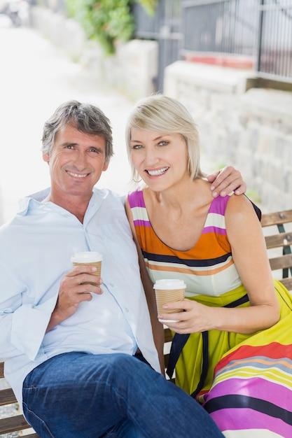 Retrato de casal com café no banco Foto Premium