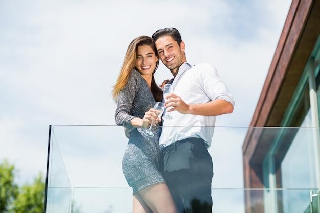 Retrato de casal feliz com champanhe na varanda Foto Premium