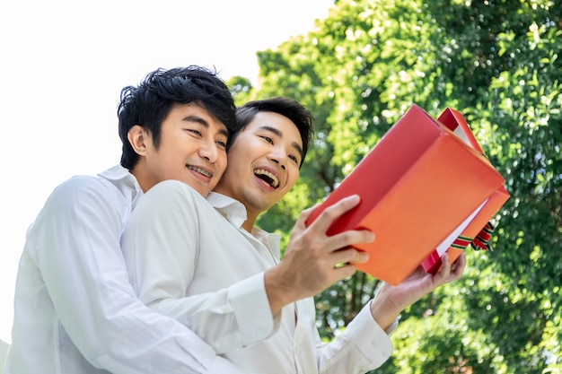 Retrato de casal homossexual asiático abraço e surpresa caixa de presente para namorado Foto Premium