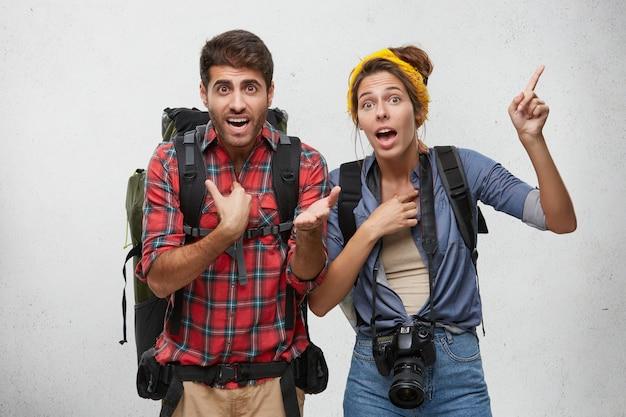 Retrato de casal jovem agitado com mochilas, gesticulando ativamente, tentando se explicar enquanto se atrasa para o avião, olhando preocupado. linguagem corporal. conceito de turismo, viagens e aventura Foto gratuita
