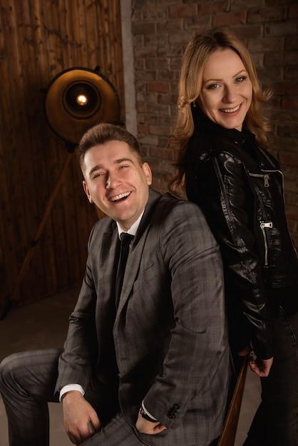 Retrato de casal jovem bonito de terno e jaqueta de couro, abraçando e sorrindo Foto Premium