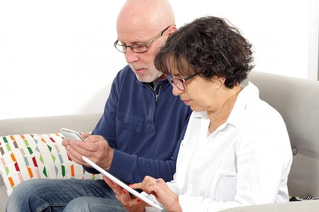 Retrato de casal sênior feliz usando tablet e telefone Foto Premium