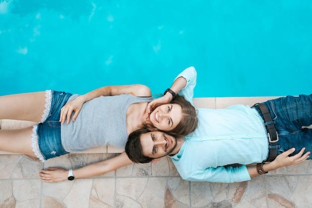 Retrato de casal sorridente deitado vestido perto da piscina. eles se adoram Foto gratuita