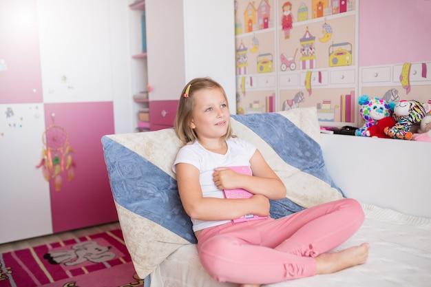 Retrato de caucasiano adolescente sonhando no quarto dela, segurando o livro nas mãos Foto Premium