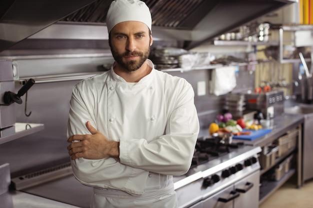 Retrato de chef confiante em pé com os braços cruzados em uma cozinha comercial Foto Premium