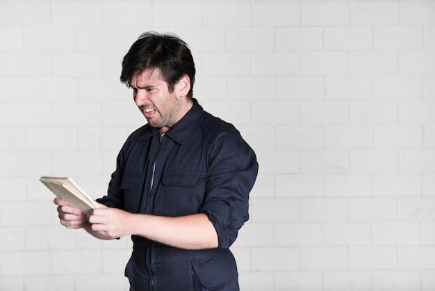 Retrato, de, chocado, eletricista, olhar livro Foto gratuita