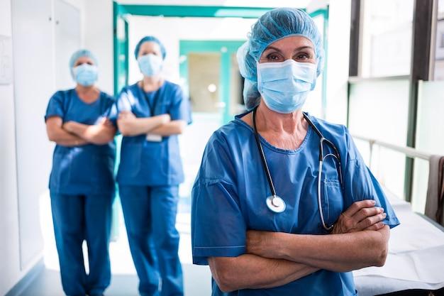 Retrato de cirurgião e enfermeiros em pé com os braços cruzados Foto Premium