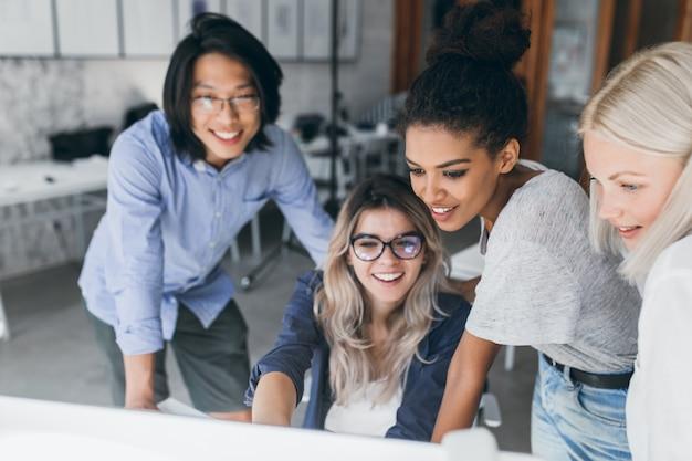 Retrato de close-up de especialistas em ti freelance olhando para a tela do laptop com um sorriso Foto gratuita