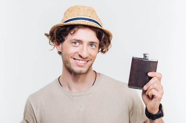 Retrato de close-up de um jovem feliz segurando um frasco de álcool isolado no fundo branco Foto Premium