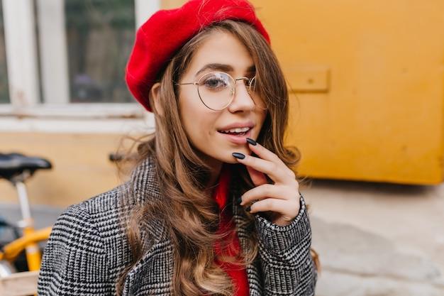 Retrato de close-up de uma curiosa mulher branca em uma boina vermelha da moda Foto gratuita
