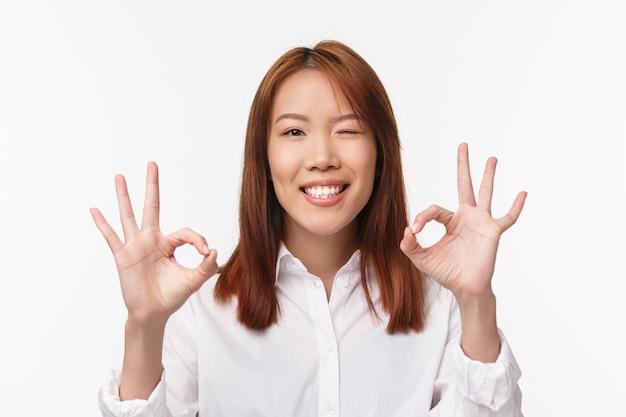 Retrato de close-up satisfeito menina bonita asiática dizer não há problema, garantir a qualidade do produto, piscadela assegurando e sorrindo com expressão satisfeita, faça um gesto bem, muito bom, Foto Premium