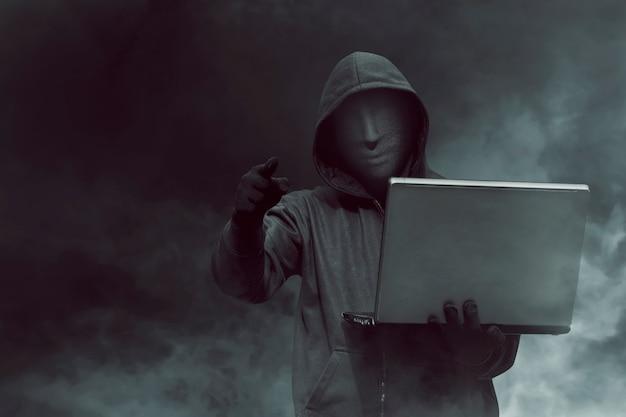 Retrato, de, com capuz, hacker, com, máscara, segurando, laptop, enquanto, ficar Foto Premium