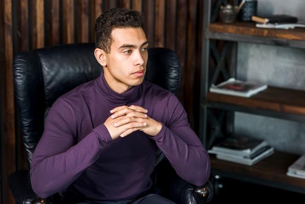 Retrato, de, contemplado, macho jovem, desgastes, roxo, polo, pescoço, sentando, ligado, poltrona, olhando Foto gratuita