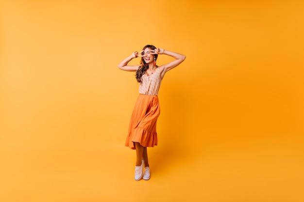 Retrato de corpo inteiro da menina elegante emocional dançando na luz. senhora jocund em saia longa laranja expressando felicidade. Foto gratuita
