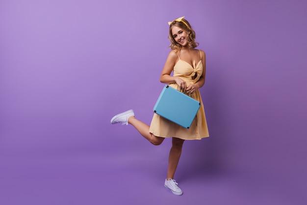 Retrato de corpo inteiro de menina bronzeada satisfeita com mala azul. mulher atraente em um vestido amarelo de pé em uma perna. Foto gratuita