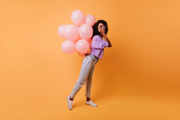Retrato de corpo inteiro de mulher africana feliz esperando a festa. modelo feminino espetacular com penteado encaracolado, expressando felicidade em seu aniversário. Foto gratuita