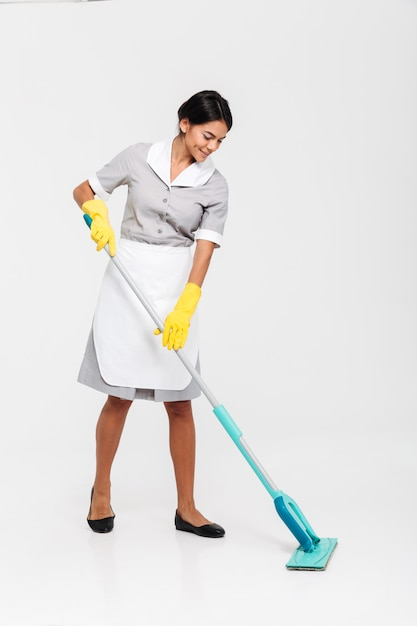 Retrato de corpo inteiro de mulher jovem e atraente em uniforme limpeza de chão com esfregão Foto gratuita
