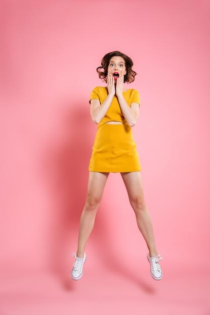 Retrato de corpo inteiro de mulher jovem e atraente espantado tocando suas bochechas, ao saltar sobre rosa Foto gratuita