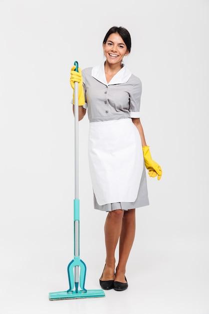 Retrato de corpo inteiro de mulher morena alegre em luvas de uniforme e borracha em pé e segurando o esfregão Foto gratuita