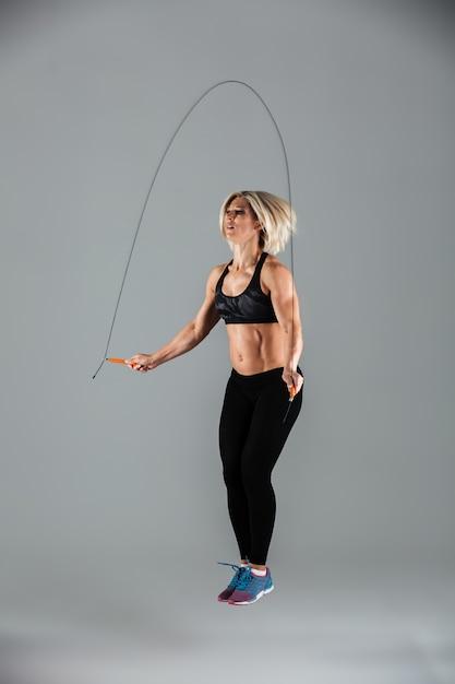 Retrato de corpo inteiro de um desportista adulto musculoso pulando Foto gratuita