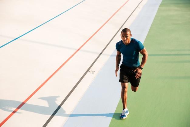 Retrato de corpo inteiro de um desportista muscular correndo Foto gratuita