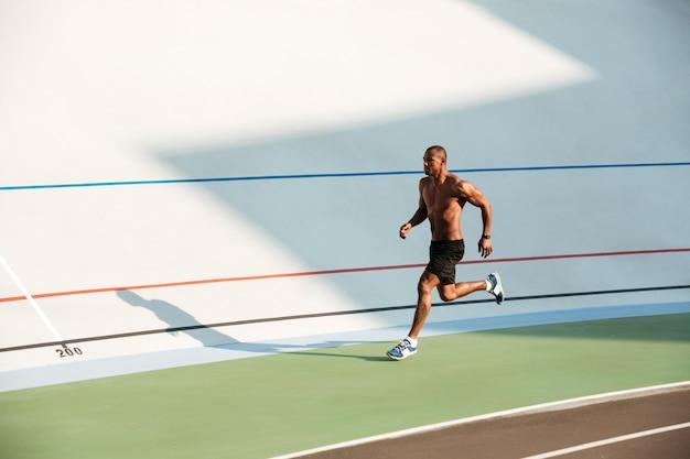 Retrato de corpo inteiro de um desportista seminu muscular Foto gratuita
