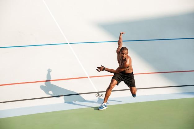 Retrato de corpo inteiro de um esportista concentrado seminu Foto gratuita