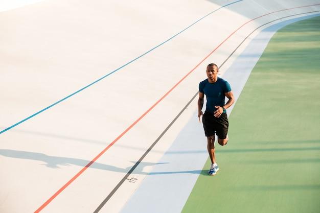 Retrato de corpo inteiro de um jovem desportista apto a correr Foto gratuita