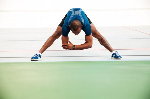 Retrato de corpo inteiro de um jovem desportista fazendo alongamento Foto gratuita