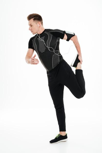 Retrato de corpo inteiro de um jovem desportista saudável, esticando as pernas Foto Premium