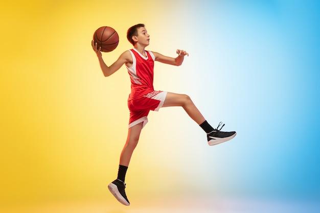 Retrato de corpo inteiro de um jovem jogador de basquete com uma bola em fundo gradiente Foto gratuita