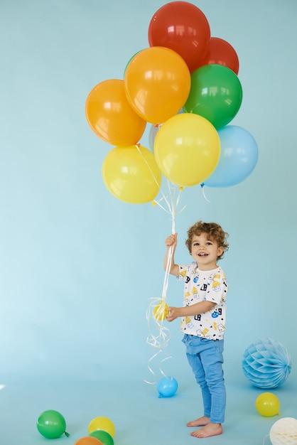 Retrato de corpo inteiro de um menino alegre segurando balons posando contra um fundo azul, conceito de festa de aniversário Foto Premium