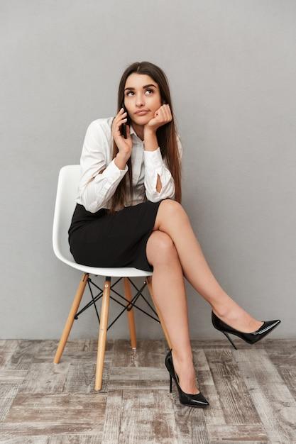 Retrato de corpo inteiro de uma adorável mulher com longos cabelos castanhos no trabalho de negócios, sentado na cadeira com uma aparência chata e tendo uma conversa móvel, isolado sobre a parede cinza Foto Premium