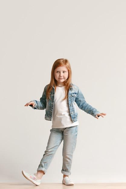 Retrato de corpo inteiro de uma criança fofa com roupas jeans elegantes, olhando para a câmera e sorrindo Foto gratuita